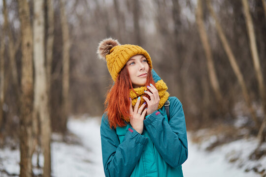 Winter portrait of a pretty young woman wearing an orange hat, scarf, and blue tracksuit. Aesthetically beautiful girl with luxurious long red hair posing in a winter forest