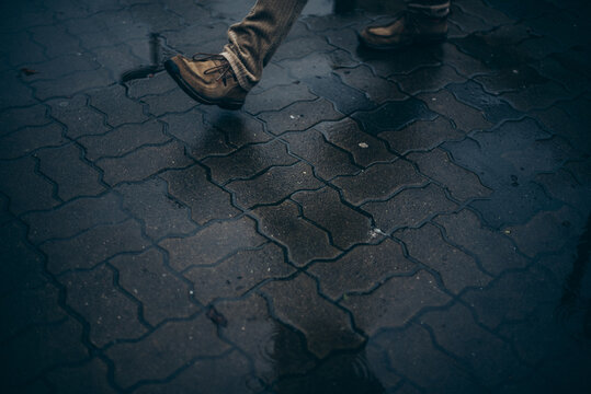 Man wearing brown shoes walking on a wet street with paving bricks pattern