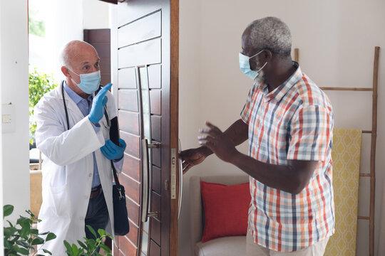 Senior african american man greeting caucasian senior doctor both wearing masks at home