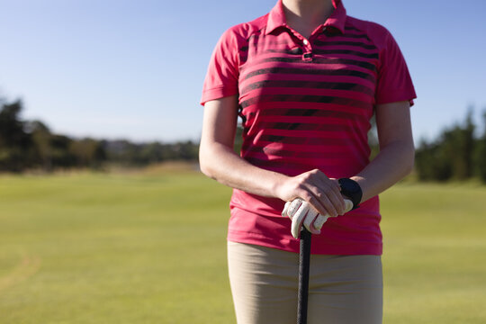 Midsection of caucasian woman standing on golf course holding golf club