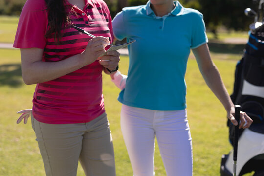 Midsection of two caucasian women playing golf one filling out scorecard