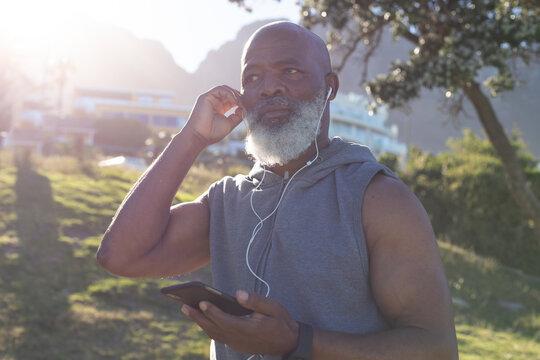 Fit senior african american man holding smartphone putting on earphones