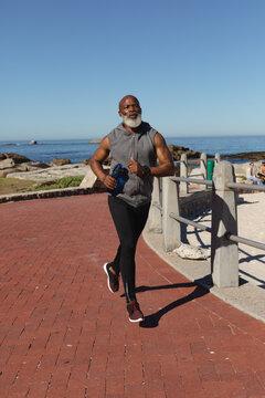 Fit senior african american man exercising running on coastal path