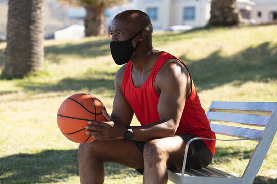 Fit senior african american man wearing face mask sitting in park holding basketball