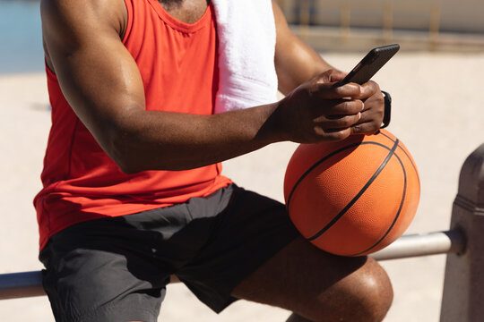 Midsection of fit senior african american man sitting in sun holding basketball using smartphone