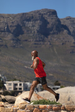 Fit senior african american man exercising running on rocky path beside mountain