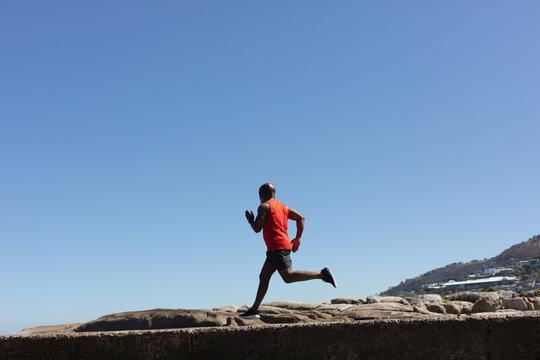 Fit senior african american man exercising running on rocky coastal path