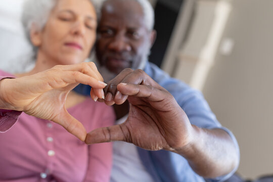 Senior mixed race couple in living room embracing making a heart shape with their hands
