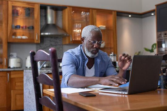 Senior african american man using laptop paying bills in dining room