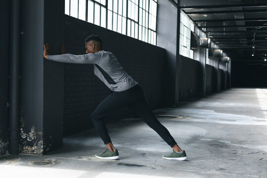 African american man leaning on a wall in an empty urban building and stretching