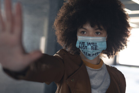 Mixed race woman wearing face mask with slogan holding her hand straight