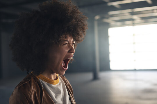 Mixed race woman standing in empty building and shouting