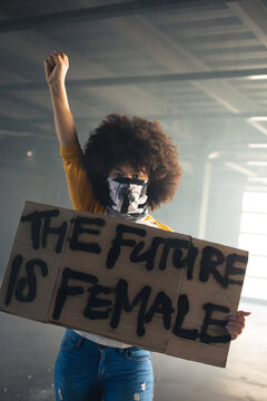 Mixed race woman wearing face mask holding protest sign raising hand up