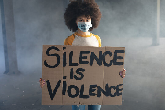 Mixed race woman wearing face mask with slogan holding protest sign