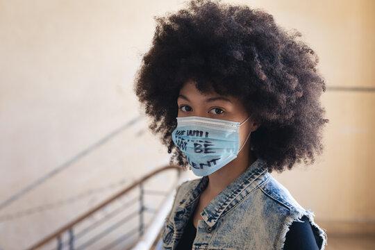 Mixed race woman wearing face mask with slogan looking at camera