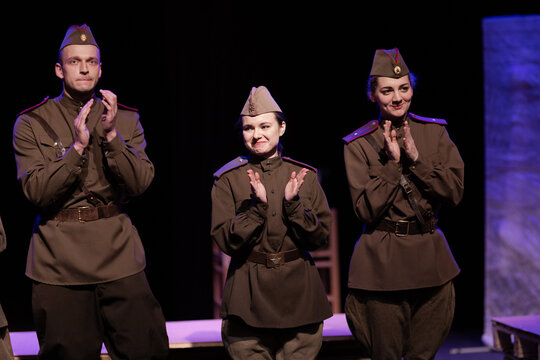 Actors in military uniforms of the Soviet army of World War II play a performance on stage in the theater