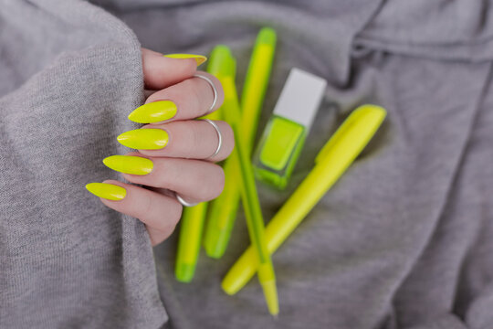 Female hand with long nails and a bottle of bright neon yellow nail polish