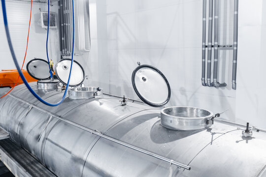 Milk tanker truck pumps products into steel storage tanks, dairy factory industry