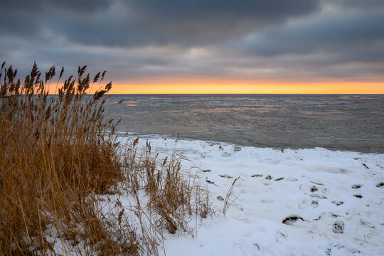 Snow covered beach at sunset, winter landscape in Jastarnia on the coast of the Hel Peninsula. Poland