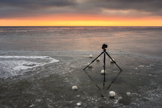 Frozen Baltic Sea during sunset. Camera on a tripod for landscape photography.