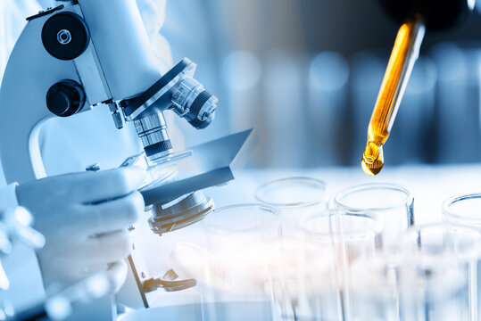 Microscope with laboratory glassware, science research and development concept, dropping chemical liquid to teat tube in lab.