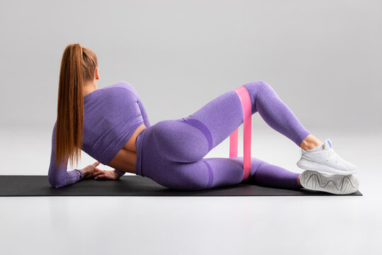 Fitness woman doing clamshell exercise for glutes with resistance band on gray background. Athletic girl working out