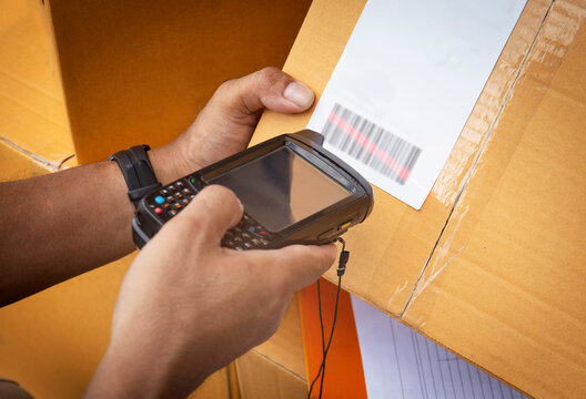 Worker holding barcode scanner scanning red laser on parcel box. Computer tools for warehouse inventory management.