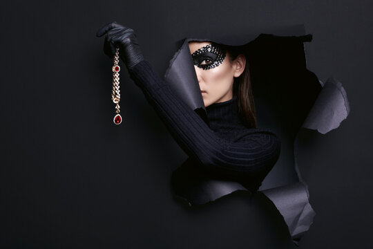 Elegant brunette woman in sequins mask posing with a stolen diamond necklace