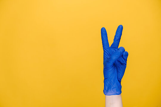 Close up of female hand in medical protective latex glove showing victory sign, isolated on yellow studio background with copy space for advertisement. Stay strong and cheerful during a quarantine