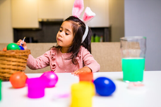 hispanic happy baby painting eggs in kitchen in modern home