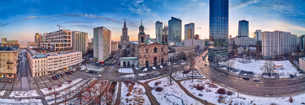 Beautiful panoramic aerial drone view on All Saints Church - Roman Catholic church located at Grzybowski Square, Warsaw City Skyscrapers, PKiN, and Varso Tower under construction. Warsaw, Poland