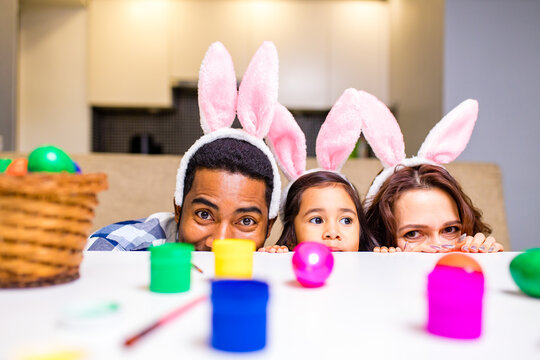 mixed race family painting eggs in cozy kitchen