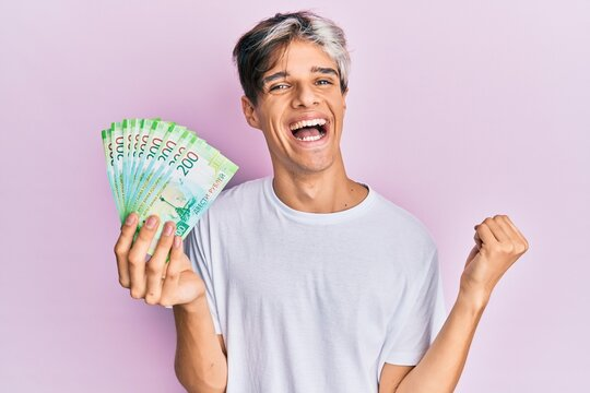 Young hispanic man holding russian 200 ruble banknotes screaming proud, celebrating victory and success very excited with raised arm