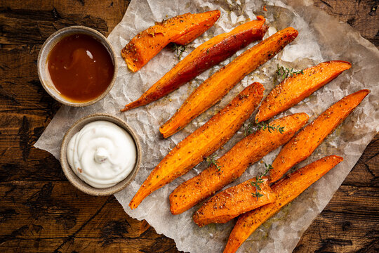 Fried sweet potato with herbs and salt served with sauces on wooden table, top view