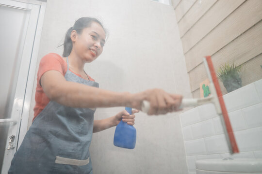 smiling Asian woman wipes using a window wiper and holds the bottle sprayer while cleaning the toilet glass in the bathroom