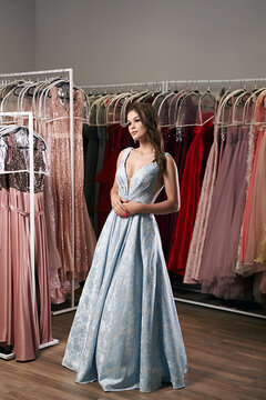 Young beautiful brunette girl wearing a full-length draped sky blue satin slit prom ball gown decorated with embroindered roses pattern. Dress hire service with many dresses on background.