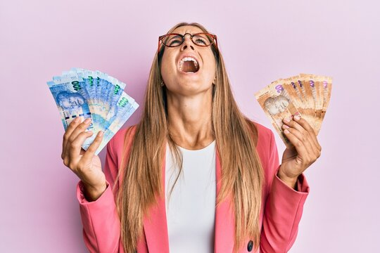 Young blonde woman wearing business style holding south african rands banknotes angry and mad screaming frustrated and furious, shouting with anger looking up.