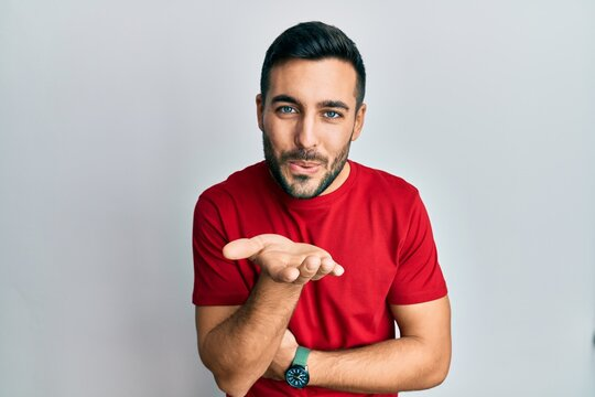 Young hispanic man wearing casual clothes looking at the camera blowing a kiss with hand on air being lovely and sexy. love expression.