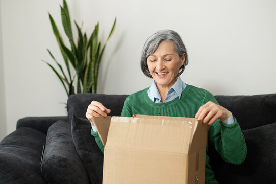 Happy smiling senior mature woman sitting on the couch with a carton box, unpacking it and feeling curious and excited about her order from an online store,delivering items during the pandemic concept
