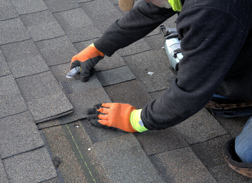 Roofer cuts a shingle to fit during repair work on a residential roof.