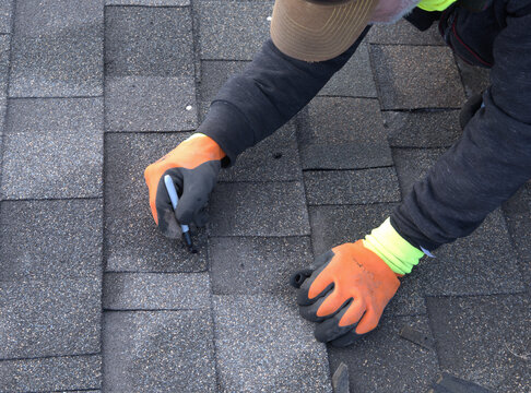 Professional roofer uses a marking pen to color the nail heads black so they will blend with the shingles.
