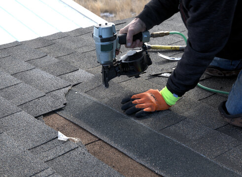 Closeup of profesional roofer using a pneumatic nail gun to fasten new shingles in place on a roof.