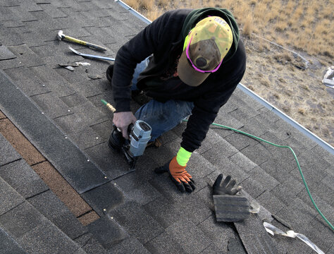 Professional roofer uses a nailer to put new shingles on a damaged roof.