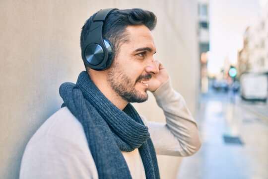 Young hispanic man smiling happy listening to music using headphones at the city.