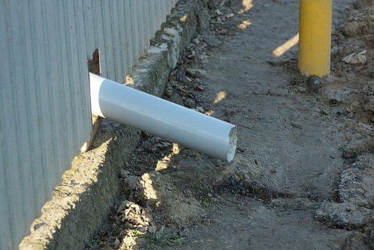 one white plastic drainpipe in a gray metal fence wall above the ground on the street