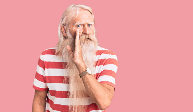 Old senior man with grey hair and long beard wearing striped tshirt hand on mouth telling secret rumor, whispering malicious talk conversation
