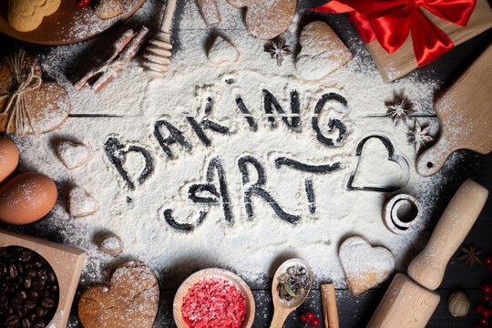 Baking Art written on flour. Gingerbread heart shaped cookies, spices, baking supplies on black wood background