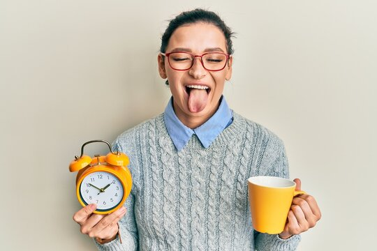 Young caucasian woman holding alarm clock drinking coffee sticking tongue out happy with funny expression.