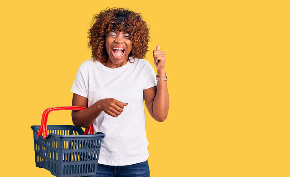 Young african american woman holding supermarket shopping basket screaming proud, celebrating victory and success very excited with raised arms