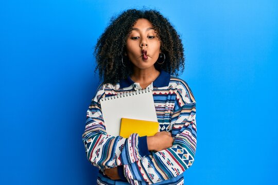 Beautiful african american woman with afro hair holding books making fish face with mouth and squinting eyes, crazy and comical.